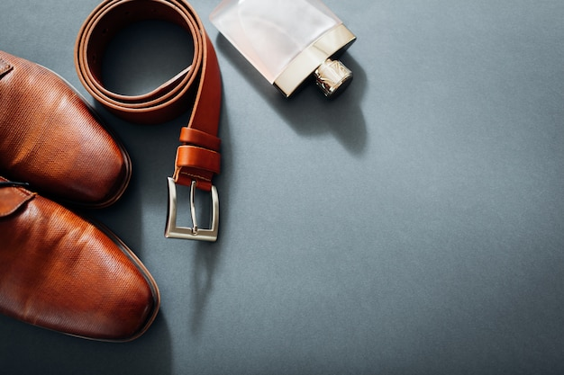 Businessman's accessories. brown leather shoes, belt, perfume, golden rings. Premium Photo