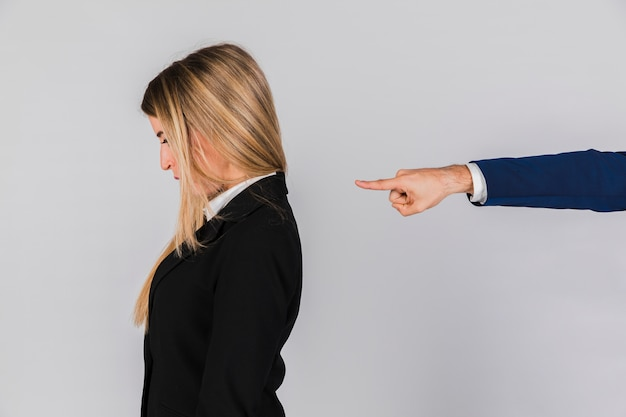 A businessman's hand blaming to young businesswoman against grey backdrop Free Photo