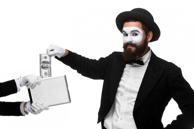 Businessman's hand in the form of mime extract money from tablet pc Free Photo