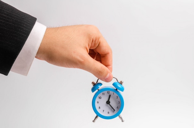 A businessman's hand holds a blue alarm clock on a white background. Premium Photo