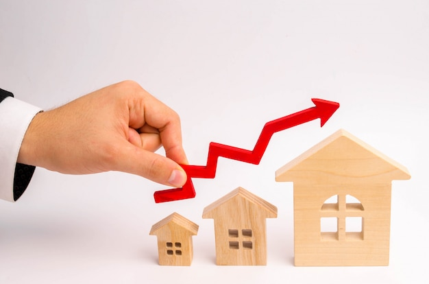Businessman's hand holds the red arrow up above the houses. growth in demand Premium Photo