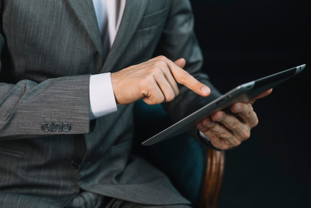 Businessman's hand touching the digital tablet screen with finger Free Photo
