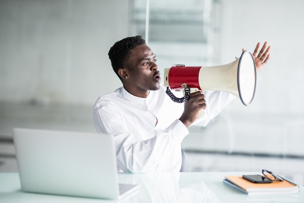 Businessman scream yelling through a megaphone in the office Free Photo