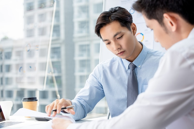 Businessman seriously discussing project with partner at office Premium Photo
