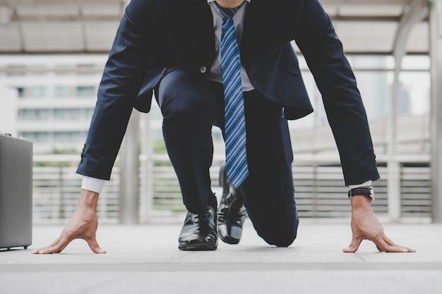 Бизнесмен в стартовом положении готовится к борьбе в деловой гонке. Premium Фотографии