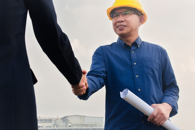 Businessman shake hands engineer construction success construction building project, hand shake agreement Premium Photo