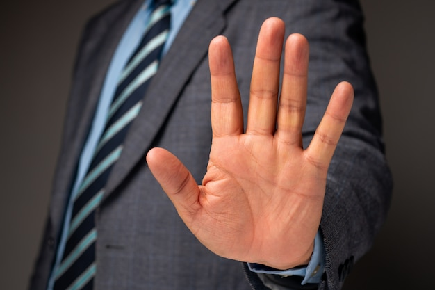 Businessman show hand sign for stop and holding, concept of professional warning for stop new investment in world crisis Premium Photo