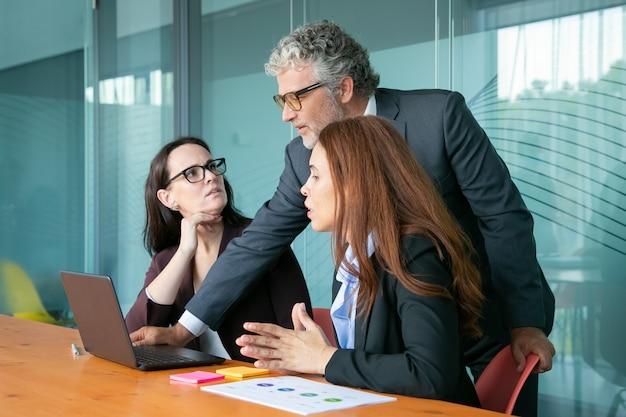 実業家のpcでプレゼンテーションを従業員に示します。 無料写真