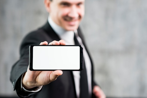 Businessman showing smartphone with clear display Free Photo