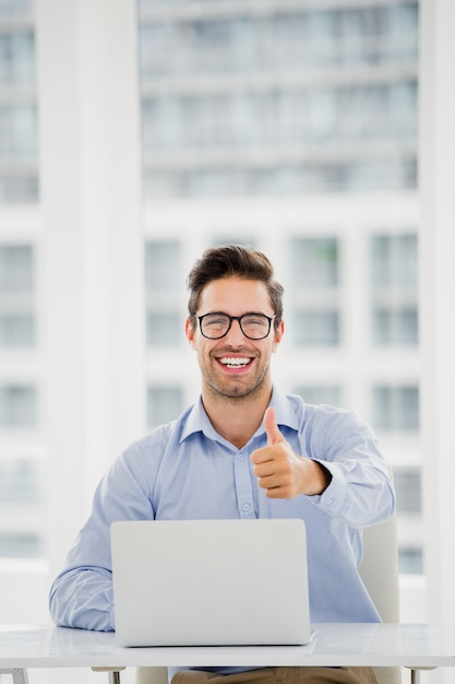 Businessman showing thumbs up while using laptop Premium Photo