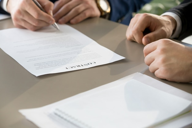 Businessman signing contract at meeting, focus on document, clos Free Photo
