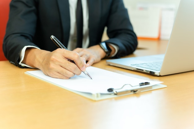 Businessman signing contract paper with pen and laptop in office desk. Premium Photo