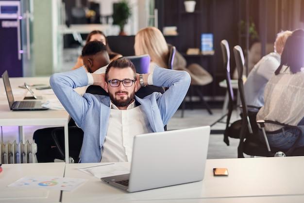 Бизнесмен сидит на рабочем месте в современном уютном офисе, глядя на экран ноутбука чувствует себя довольным гордостью за проделанную работу, молодой человек отдыхает, положив руки за голову. нет стресса концепции. Premium Фотографии