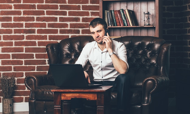 A businessman sits on the couch and calls from the phone. rich man is surrounded by a stylish interior of the room Premium Photo
