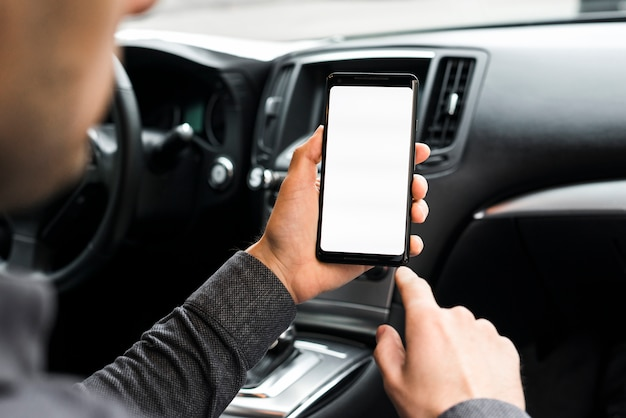 A businessman sitting in the car using mobile phone with white display screen Free Photo