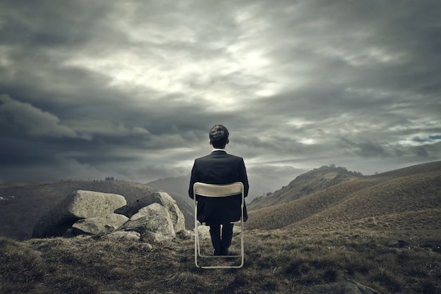 Businessman sitting on a chair on the mountain Premium Photo