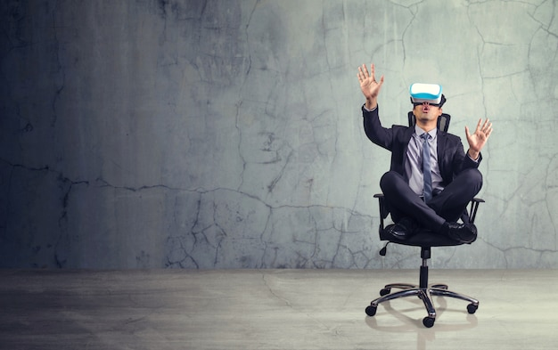 Businessman sitting in chair wearing virtual reality glasses. Premium Photo
