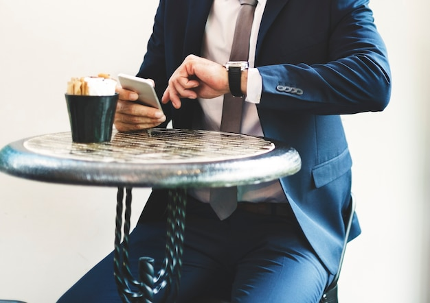 Businessman sitting checking time from wrist watch Free Photo