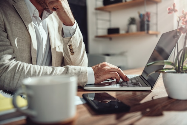 Businessman sitting at his desk and using laptop in the office Premium Photo