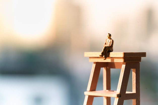 A businessman sitting on ladder with light copy space. Premium Photo