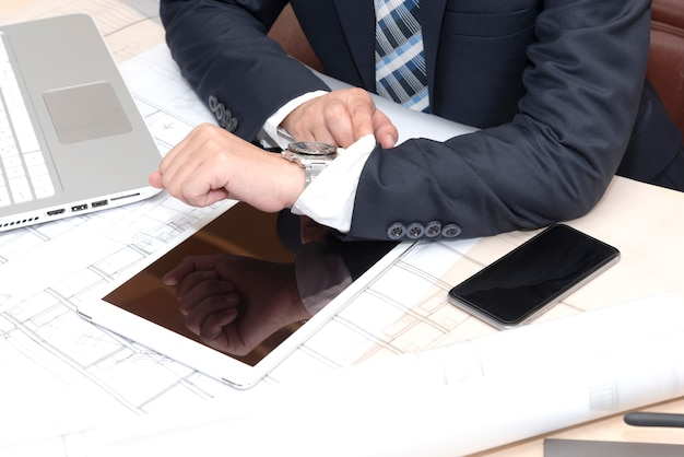Businessman sitting in the office and looking on the watch Free Photo