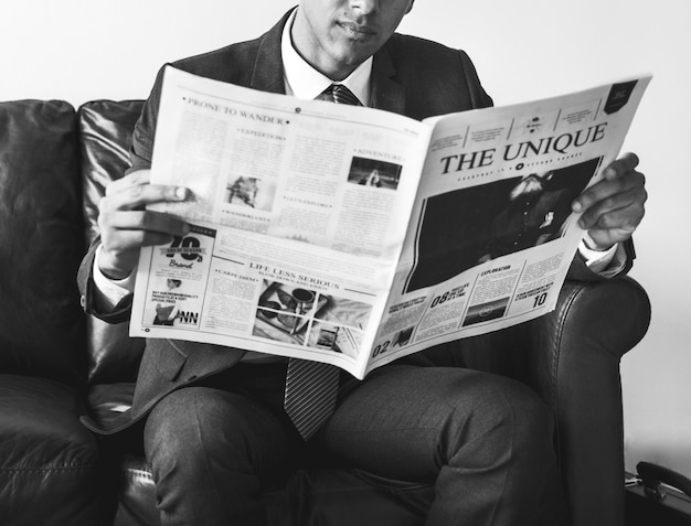 Businessman sitting and reading newspaper Free Photo