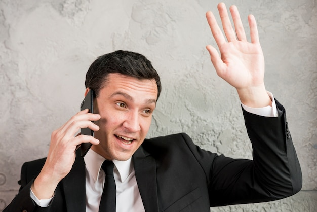 Businessman speaking on phone and waving hand Free Photo