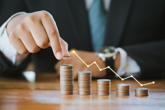 Businessman stacking coins with a graph of profit. finance savings concept Premium Photo