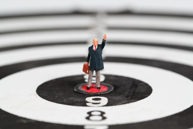 Businessman standing on dartboard target center idea of financial and business goal Premium Photo