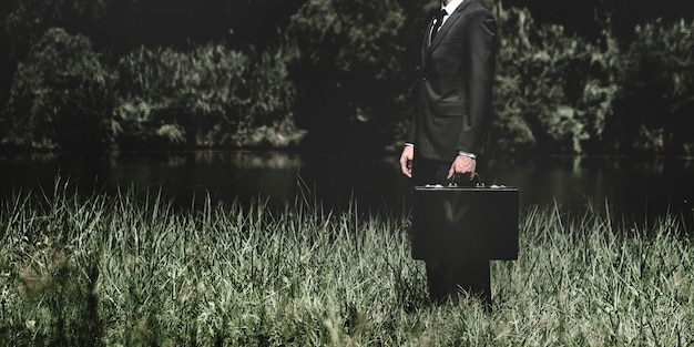 Businessman standing on a grass outdoors Free Photo