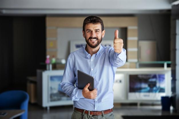 수출 회사의 로비에 서서 태블릿을 들고 엄지 손가락을 보여주는 사업가. 프리미엄 사진