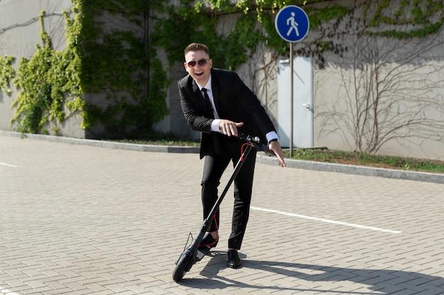 電動スクーターの隣に立っているビジネスマン Premium写真