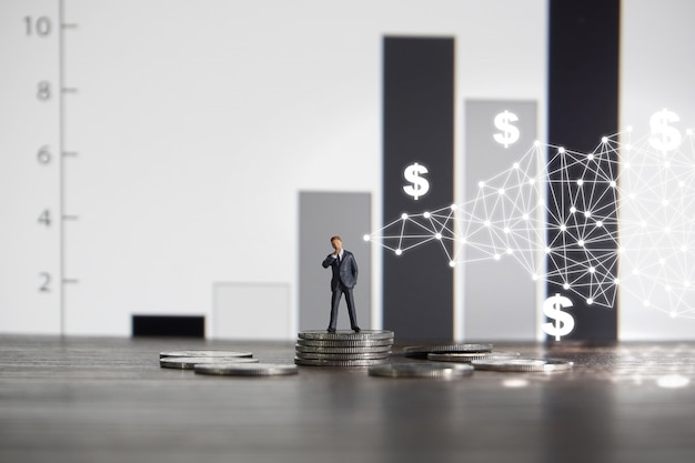 Businessman standing on a pile of coins Premium Photo
