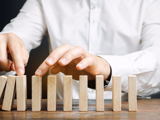 Businessman stops collapse domino effect. Premium Photo