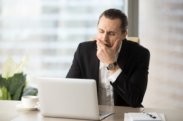 Businessman struggling with drowsiness at work Free Photo
