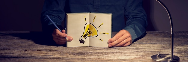 Businessman or student showing his working notebook with a handdrawn light bulb Premium Photo