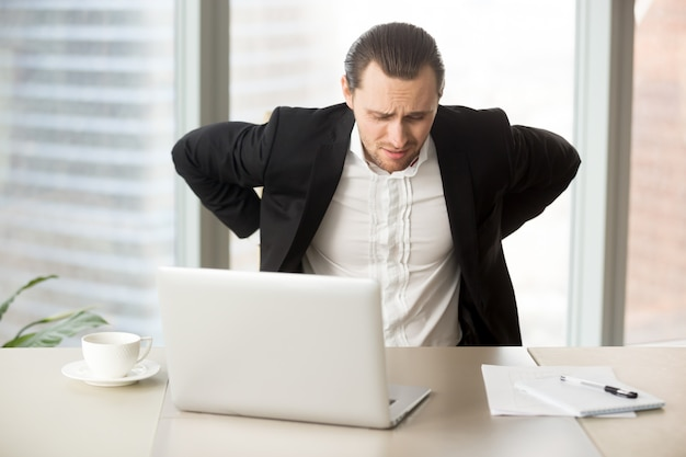 Businessman suffering from backache at workplace Free Photo
