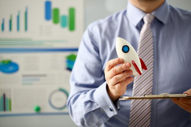 Businessman in suit hold white rockrt in hand Premium Photo