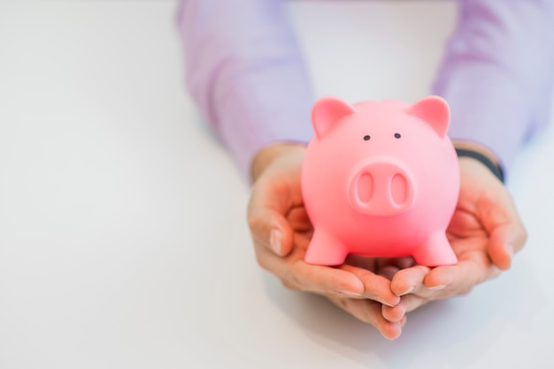 Businessman in a suit holding pink piggy bank with both hands, isolated on white background. Free Photo