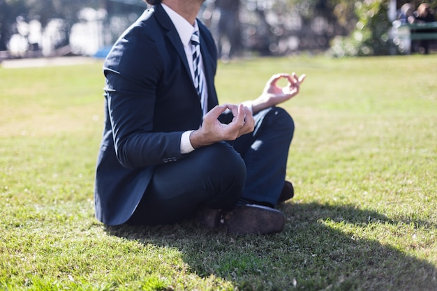Businessman in suit practicing yoga Free Photo