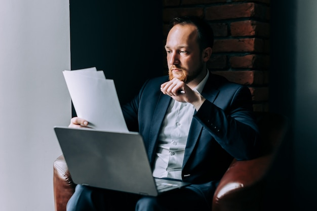 A businessman in a suit sits in an armchair with a laptop and analyzes a financial report. Premium Photo