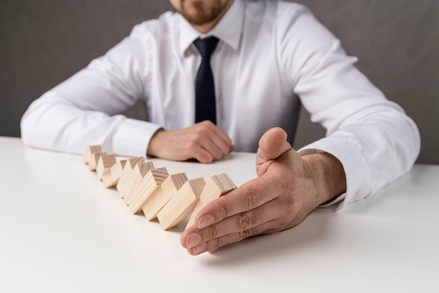 Businessman in suit and tie holding domino pieces Free Photo