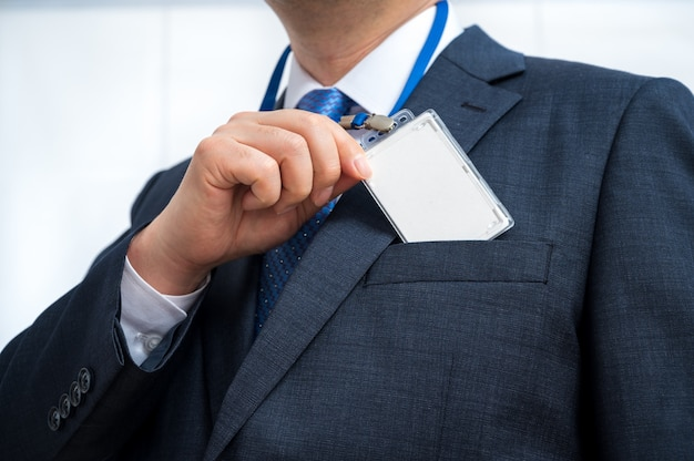 Businessman in suit wearing a blank id tag or name card on ...