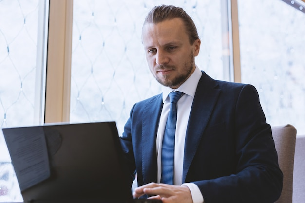 Businessman in the suit  working on the laptop sitting  at the table indoor Premium Photo