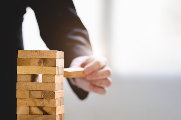 Businessman take and picking wood block on stacked tower by hand as startup project Premium Photo