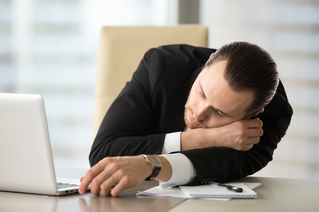 Businessman takes break and dozing in office Free Photo