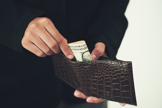 Businessman taking money out from wallet on white Premium Photo