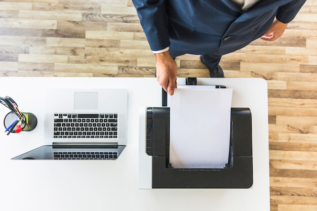 Businessman taking paper from printer in the office Free Photo