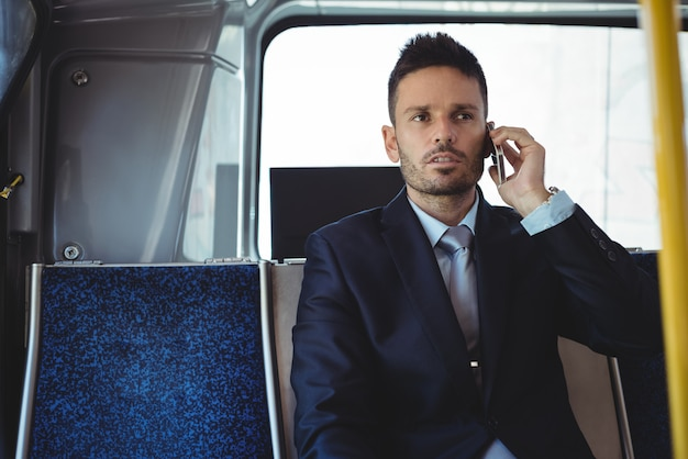 Businessman talking on the mobile phone while travelling Free Photo