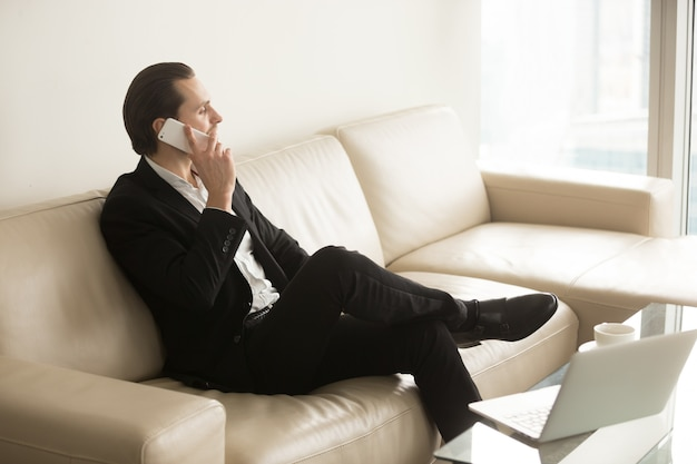 Businessman talks on the phone while sitting on couch. Free Photo